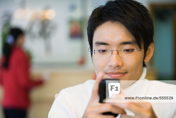 Junger Mann schaut auf das Handy  lächelnd