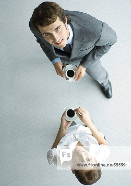 Business associates holding cups of coffee  looking up at camera  full length  high angle view