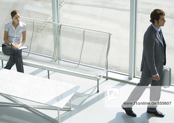 Lobby  Frau sitzend  während der Geschäftsmann mit Aktentasche vorbeikommt  volle Länge  hohe Blickwinkel