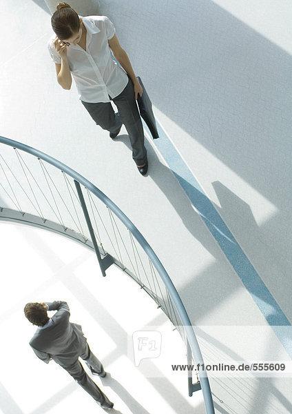 Frau mit Handy in der Nähe des Geländers  im Untergeschoss  Geschäftsmann beim Gehen mit dem Handy  Hochwinkelansicht