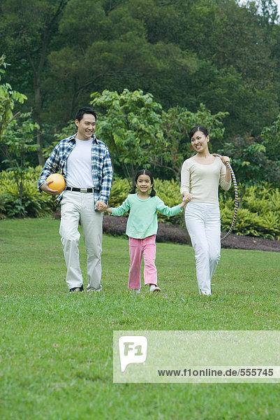 Mädchen  das mit den Eltern über das Gras läuft