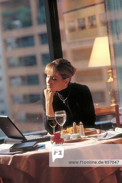 Geschäftsfrau arbeiten mit Laptop während dem Frühstück in einem Hotelzimmer