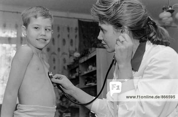 Kinderarzt examining Kind