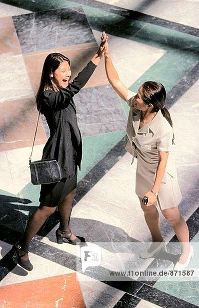 Geschäftsfrauen feiern mit einer High-Five-Begrüßung