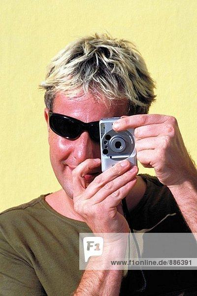 Aufnahme eines Bildes mit einer kleinen Kamera Mann
