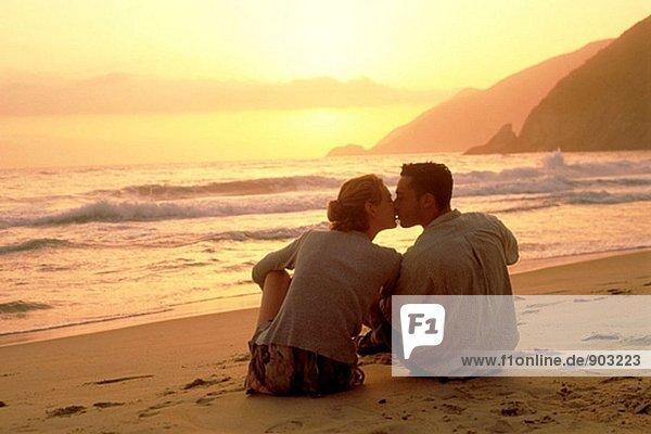Junges paar sitzen auf Sand am Strand an Sun küssen