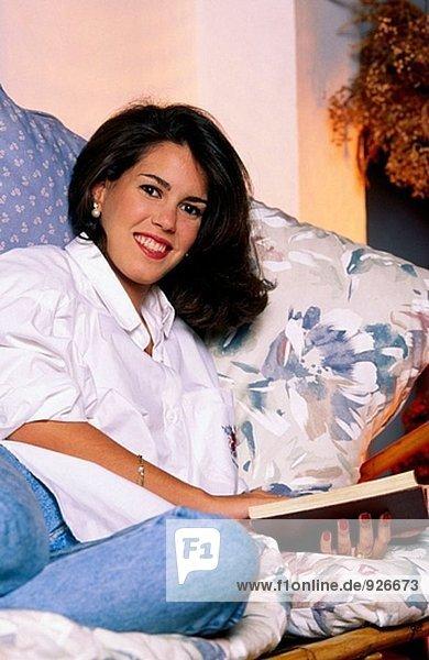 Frau sitzt auf einem Sofa  ein Buch zu lesen