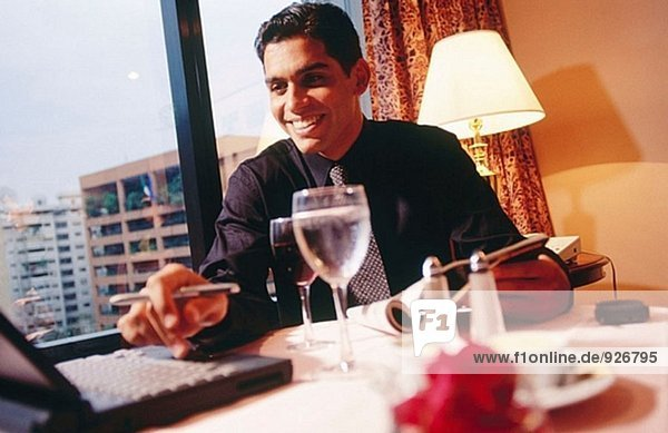 Businessman working with laptop computer on a table in a hotel room