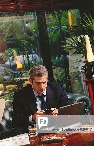 Kaufmann arbeiten mit Laptop-Computer und PalmPilot in einer Hotellounge