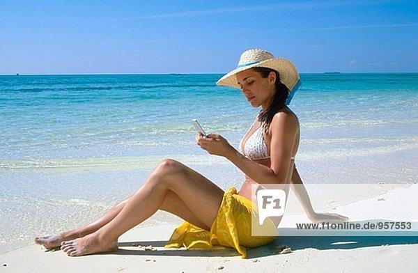 Frau mit eine Mobile auf einem Strand. White Sands Resort und Spa. Ari Atoll. Malediven