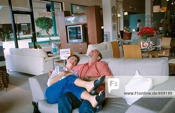 Paar umarmt auf einem Sofa in einem Möbelhaus