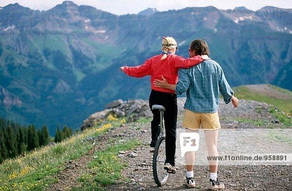 Mann Frau beizubringen  wie man ein ´monocycle´ auf Top Mountain fahren. Colorado. USA