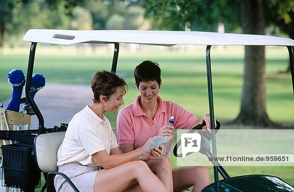 gwo women checking their scorecard on golf course