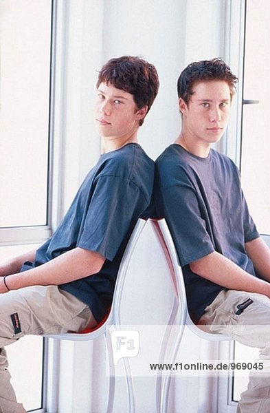 Twin teenage boys sitting in contemporary chairs