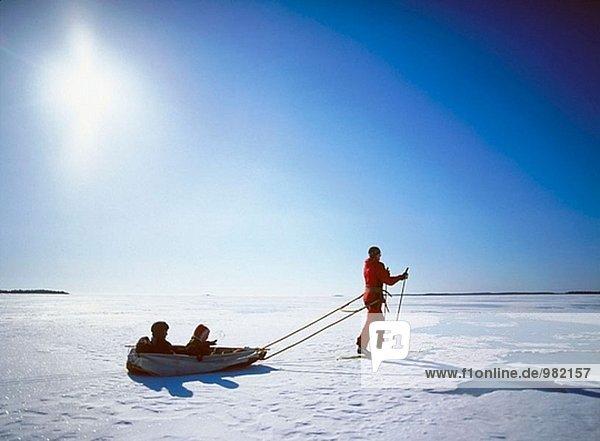 Frau Skifahren mit zwei Kindern in einen Schlitten in direktem Licht. Västerbotten  Schweden