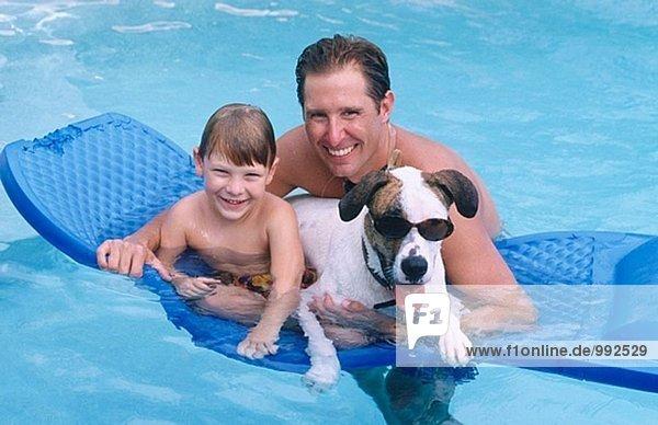 Vater/Sohn mit lustigen Hund im pool
