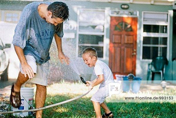 Vater und Sohn haben eine Wasserschlacht