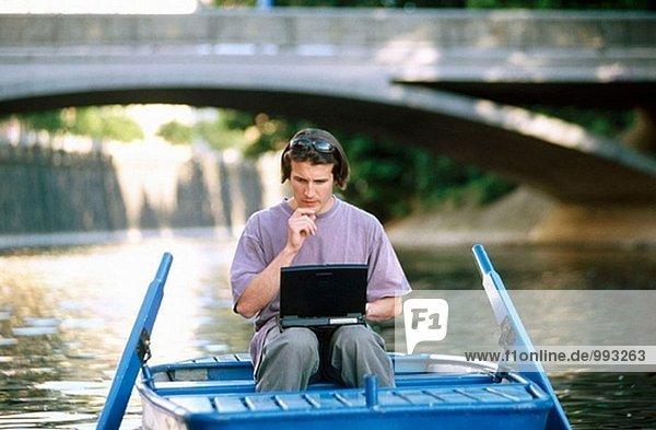 Man on rowboat using laptop