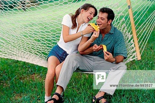 Paar in einer Hängematte Essen Mangos