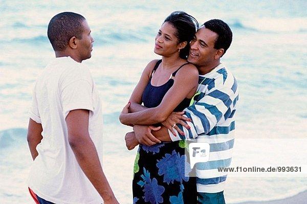 Paar und einen Freund sprechen am Strand