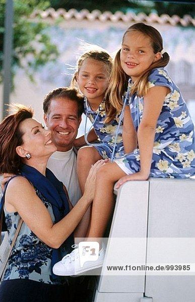 Familie mit Zwillingsmädchen an einem Geldautomaten