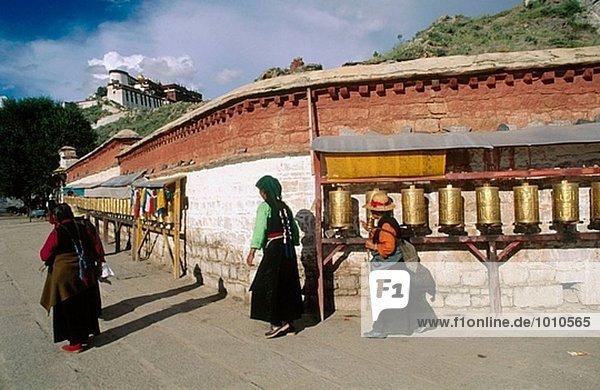 Prayer mills. Potala Palace in background. Lhasa. Tibet. China.