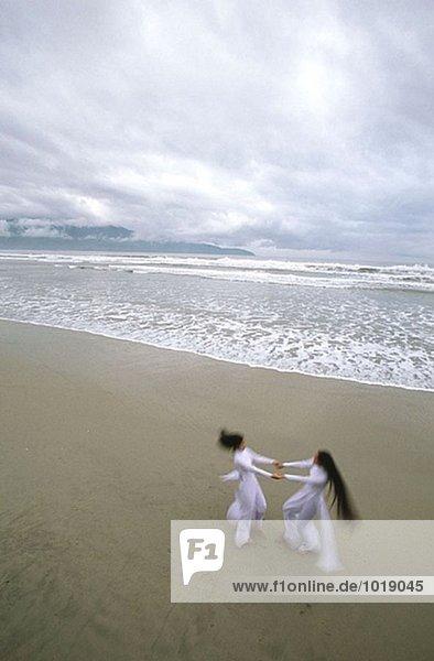 Zwei Schülerinnen in Nationaltracht Tanz am Strand als tropischer Sturm sammelt Danang´s Küste. Provinz Quang Nam. Vietnam. Zwei Schülerinnen in Nationaltracht Tanz am Strand als tropischer Sturm sammelt Danang´s Küste. Provinz Quang Nam. Vietnam.