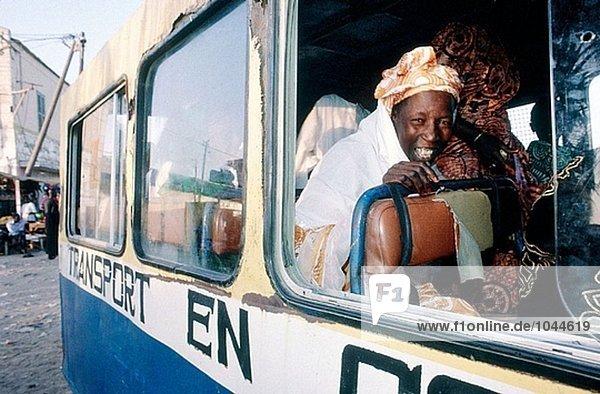 glückliche Frau innerhalb der lokalen Bus (Auto Rapide) Passagiere warten. Saint Louis Altstadt. Senegal