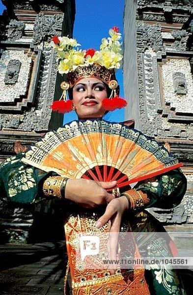 Junge Tänzerin ausführen Legong Kraton (Palace Tanz) durch eine Temple-Tor. Bali Insel. Indonesien
