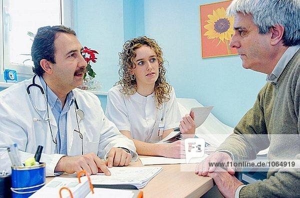 Arzt und Krankenschwester mit Patienten im Doctor´s Büro des Krankenhauses