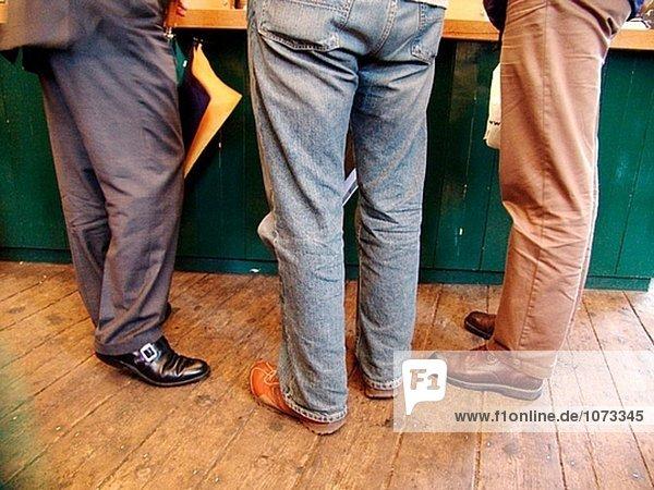 Drei Männer in verschiedenen Kleidung-ein Anzug  Jeans und casual Hosen-Stand in einer Bar bestellen Kaffee in London. Ein Mann hält einen Regenschirm.