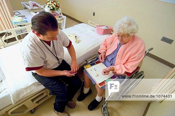 Senior Frau arbeitet mit Physiotherapeutin an Schlaganfall