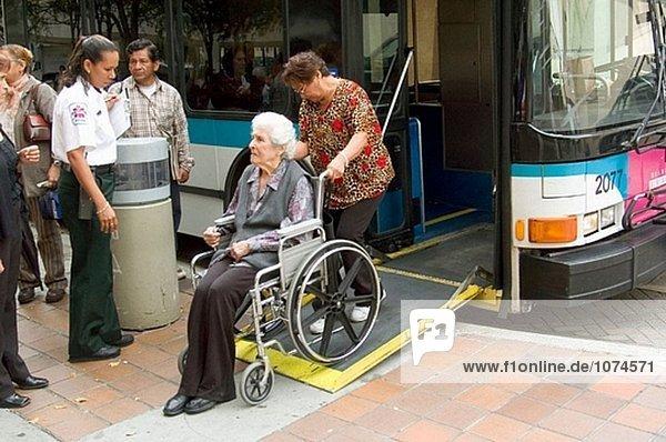 Behinderte seniör weiblich im Rollstuhl boarding Stadtbus  Straßenleben. Miami. Florida  USA