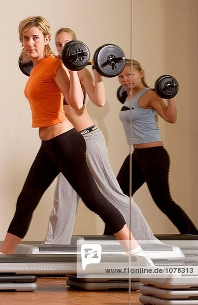 women doing weight lifting at the gym