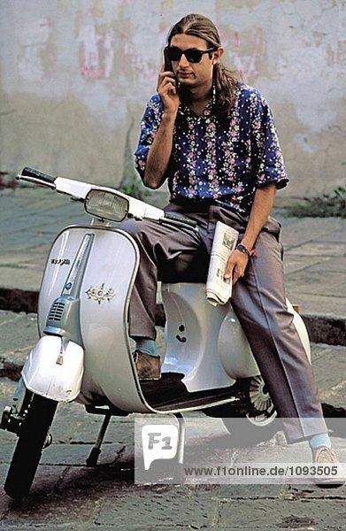 Italienischen Mann mit Handy und Vespa. Florenz  Italien