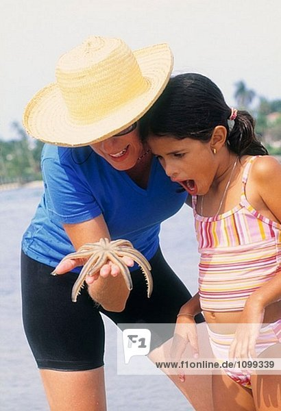 Woman showing starfish to girl at the beach