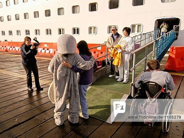 Tourists getting picture taken with ship mascot as they come off ship. Ketchikan. Alaska. USA