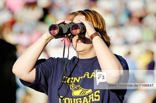 Spectator looks through binoculars at a Kenny Rogers concert