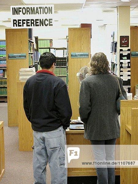 Paar versucht Hilfe am Auskunftspult in Bibliothek zu bekommen.