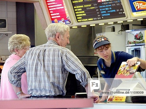 McDonald´s Mitarbeiter unterstreicht ein Produkt zu einem älteres Paar