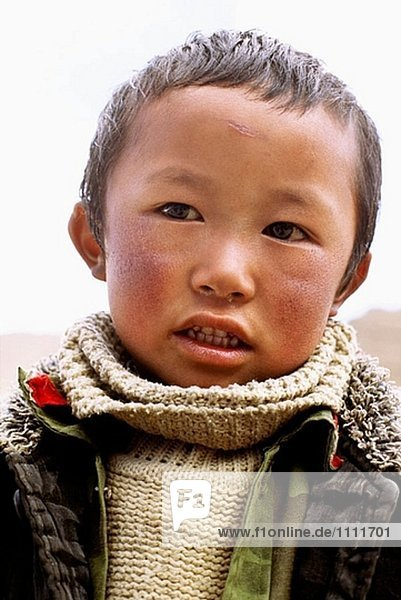 Portrait of young Tibetan Chinese boy wearing warm sweater and jacket