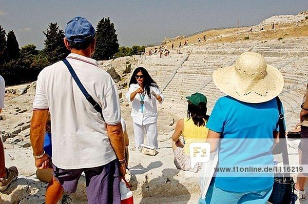 Touristen besuchen das griechischen und römischen Theater. Syrakus. Sizilien. Italien