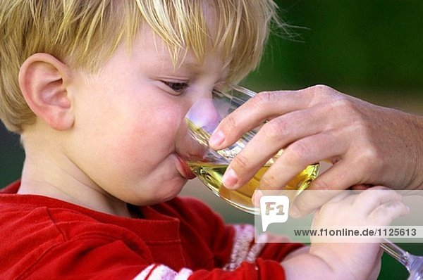 Toddler drinking from wine glass