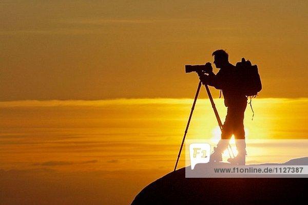 Fotograf mit Stativ silhouetted auf Felsen bei Sonnenuntergang. Norwegen.