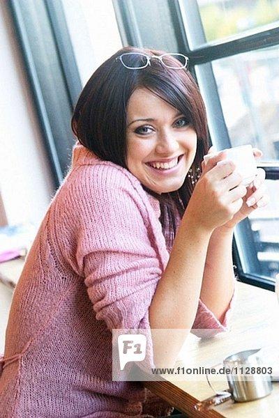 21 Einjahresmädchen  sitzen in bar  Lächeln in die Kamera  halten eine Tasse Kaffee