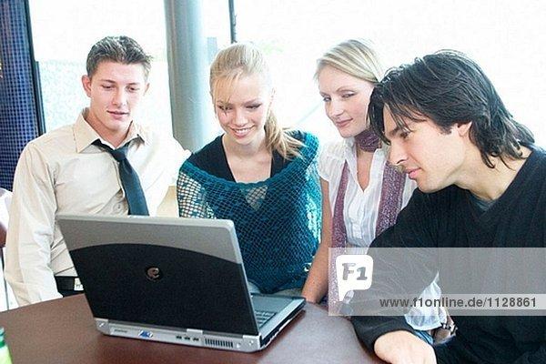 Gruppe von jungen Menschen  sitzen an einem Tisch in einem Café  Blick in einen laptop