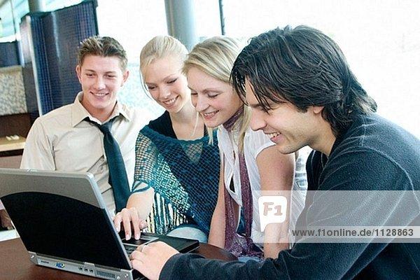 Gruppe von Jugendlichen  sitzen an einem Tisch in einem Café  Blick auf einem Laptop lächelnd