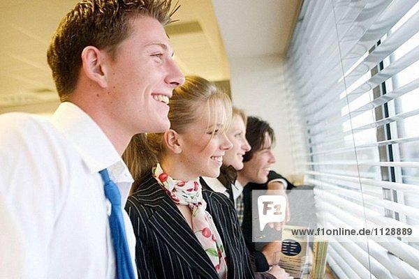 4 jungen Geschäftsleute stehen in einer Linie Blick aus dem Fenster  geringe Tiefenschärfe