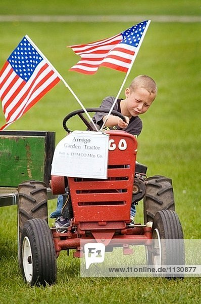 Kleiner Junge Pretents  einen kleinen Traktor mit amerikanischen Flaggen an es angeschlossen zu fahren