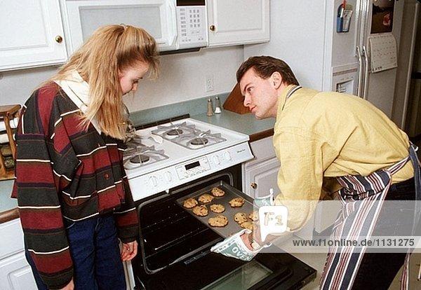 Ehemann backt Cookies während Frau blickt auf